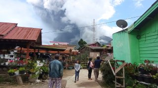 People watch as Mount Sinabung spews volcanic materials during an eruption in Karo, North Sumatra, Indonesia
