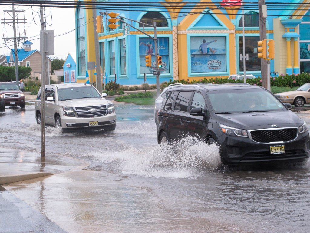 This Oct. 11, 2019 photo shows cars kicking up spray while driving through a flooded intersection at the entrance to Long Beach Island in Ship Bottom, N.J. With the highest tides of the year expected to arrive in New Jersey during the week of May 24, 2021, the state is launching a campaign to have residents document tidal flooding in their neighborhood and upload photos to a web site.