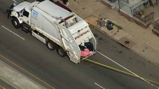 Philadelphia trash truck with police tape blocking off te roadway behind it after a body was found by sanitation workers on July 1, 2021,
