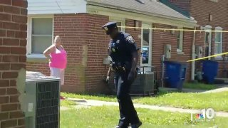 """A Wilmington police officer walks across a lawn as a woman watches on during the investigation into the shooting death of TikTok creator Matima Miller, known by his nickname, """"Swavy."""""""