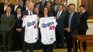 President Biden and Vice President Harris hold jerseys presented to them by the Dodgers.