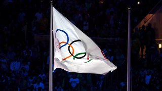 The Olympic flag atop a flag pole