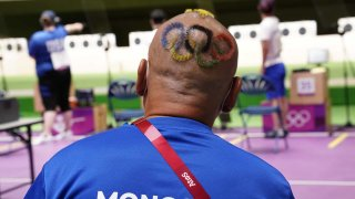 Mongolian shooting coach with hair cut into Olympic rings