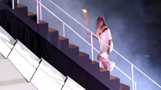 Naomi Osaka carries a torch to the cauldron inside Olympic Stadium before lighting the Olympic flame at the Opening Ceremony of the Tokyo Olympic Games.