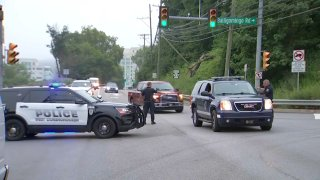 Police officers and patrol SUVs block off a road and divert cars.