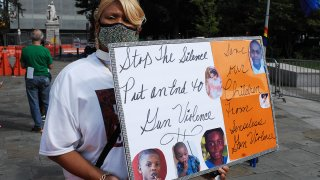 A woman holds a sign calling for an end to violence