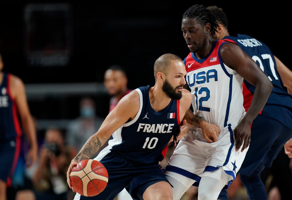 France's Evan Fournier (10) drives past United States' Jrue Holiday (12) during Men's Basketball gold medal game at the 2020 Olympics, Saturday, Aug. 7, 2021, in Saitama, Japan.