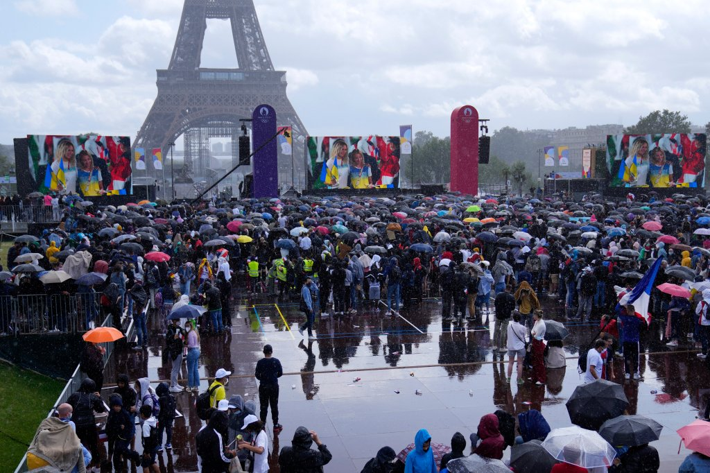 People watch the closing ceremony of the Tokyo 2020 Olympic Games on giant screens in the Olympics fan zone at Trocadero Gardens in front of the Eiffel Tower in Paris, Sunday, Aug. 8, 2021. A giant flag will be unfurled on the Eiffel Tower in Paris Sunday as part of the handover ceremony of Tokyo 2020 to Paris 2024, as Paris will be the next Summer Games host in 2024. The passing of the hosting baton will be split between the Olympic Stadium in Tokyo and a public party and concert in Paris.