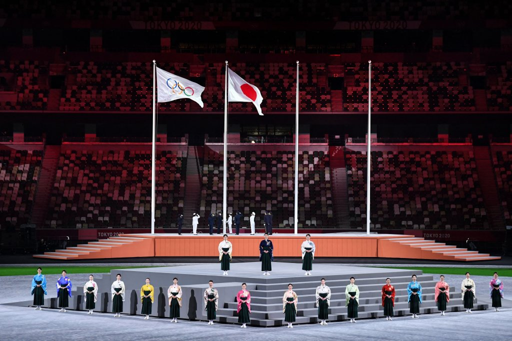 Performers sing the Japanese national anthem as the Olympic flag and Japan's flag are raised during the closing ceremony of the Tokyo 2020 Olympic Games, at the Olympic Stadium, in Tokyo, on Aug. 8, 2021.