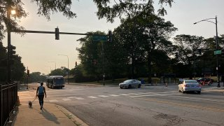FILE - In this Aug. 10, 2021, file photo, a pedestrian walks with a dog at the intersection of South Stony Island Avenue and East 63rd Street where the ShotSpotter technology is in use above the crossroads.