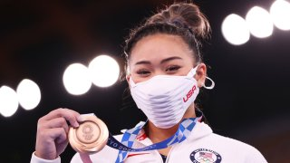 Suni Lee poses with the bronze medal she won in the uneven bars event final