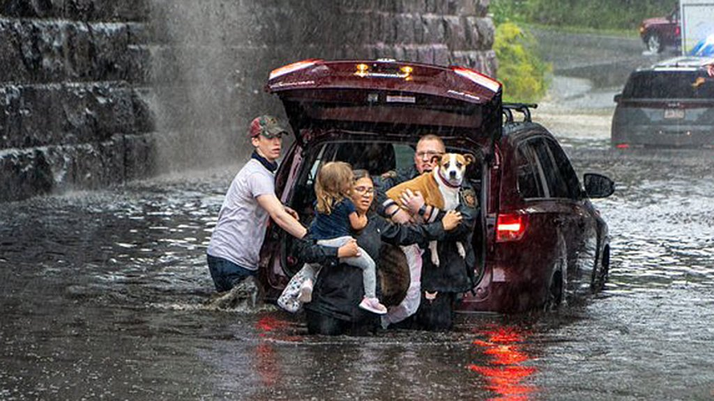 These people walk away from a flooded vehicle in Caln Township, Chester County, on Sept. 23, 2021.