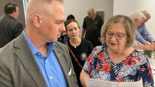 Brian Stransky, of unincorporated Sarpy County, Nebraska, listens as Citizens for Voter ID campaign official Nancy McCabe reads to him from a voter ID ballot petition