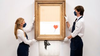 Art handlers at Sotheby's auction house hold Banksy's 'Love is in the Bin'