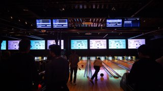 people bowling in a darkened room