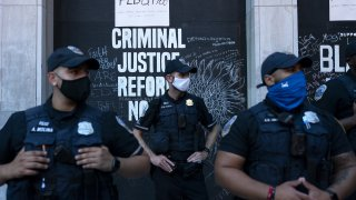 Police officers wearing protective masks stand in front of a criminal justice reform sign