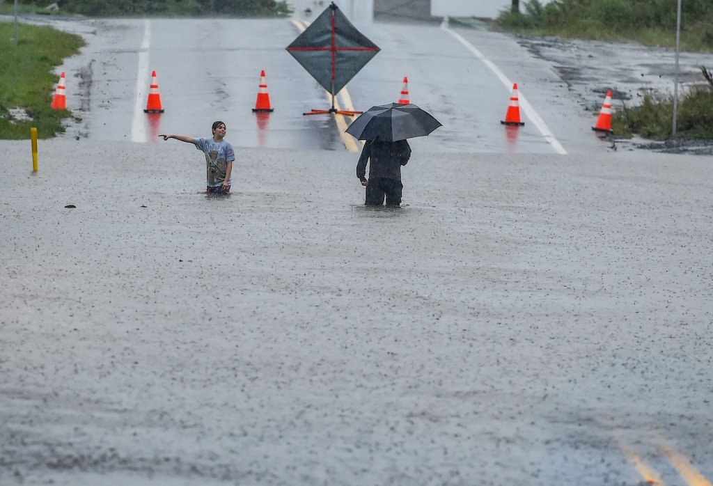 A man and young girl make their way through the flooded Main