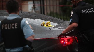 Shell casings labeled 59 and 60 rest on a bullet-riddled car as police investigate the scene of a shooting in the Auburn Gresham neighborhood on July 21, 2020 in Chicago, Illinois.