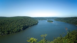 Trees line the Susquehanna River in PA, USA on a summer autumn day.