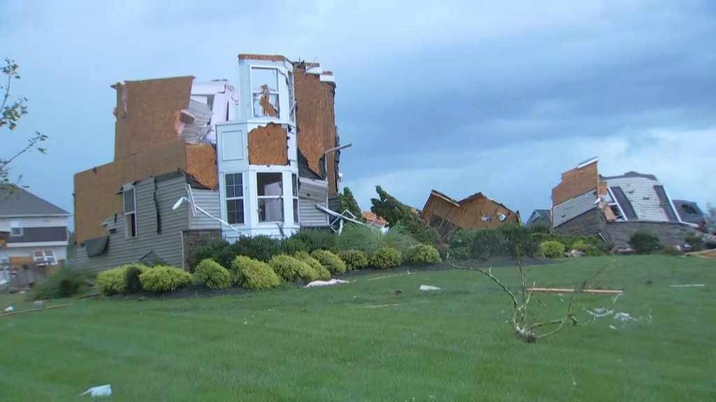 A multi-story home can be seen with its roof collapsed and blown out windows in front of a green lawn after a tornado ripped through the area.