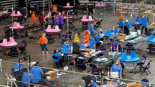 FILE - In this May 6, 2021 file photo, Maricopa County ballots cast in the 2020 general election are examined and recounted by contractors working for Florida-based company Cyber Ninjas at Veterans Memorial Coliseum in Phoenix.