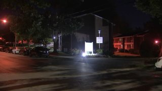 A light shines in front of a sign placed in front of a Philadelphia apartment complex.