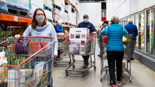 Shoppers wearing masks search for items at a Costco Wholesale store