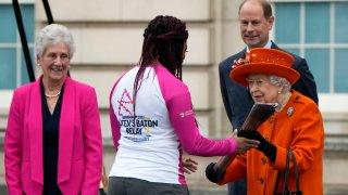 Britain's Queen Elizabeth II hands over the Queen's Baton to the first relay runner Kadeena Cox