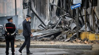 Carabinieri officers stand on the site of a plane crash, in San Donato Milanese suburb of Milan, Italy