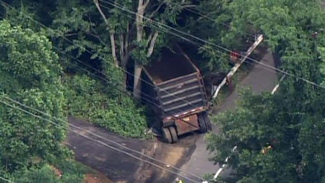 Crash Sends Dump Truck Atop Highway Rail
