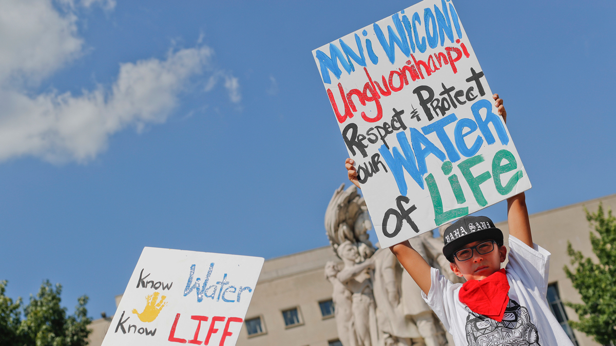 File Photo: Tusweca Mendoza, 10, of Arlington, Virginia, originally from Pine Ridge, South Dakota, holds up a sign outside U.S. District Court in Washington, Tuesday, Sept. 6, 2016. The Standing Rock Sioux Tribe have asked the Department of Justice to mediate talks between protesters and local law enforcement.