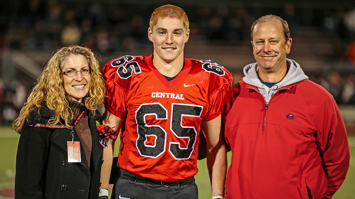This Oct. 31, 2014, photo provided by Patrick Carns shows Timothy Piazza, center, with his parents Evelyn Piazza, left, and James Piazza, right, during Hunterdon Central Regional High School football's