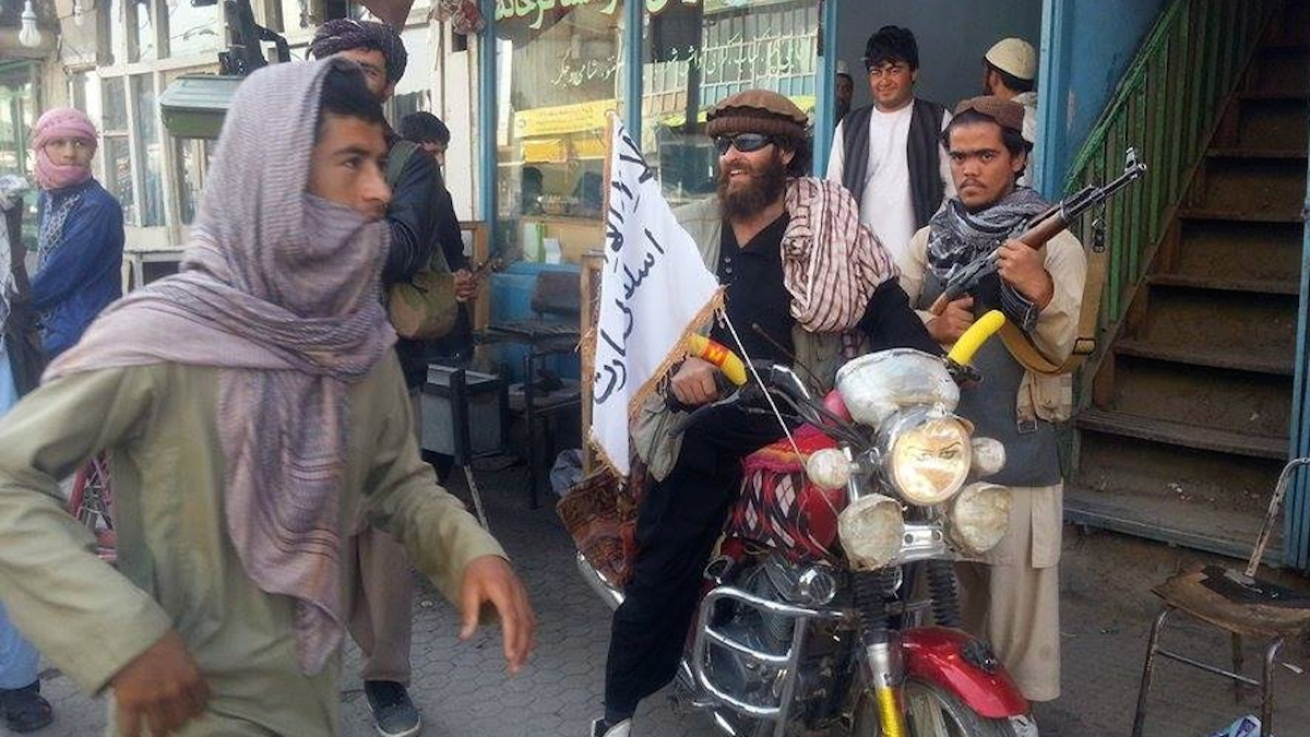 A Taliban fighter sits on his motorcycle adorned with a Taliban flag in a street in Kunduz city, north of Kabul, Afghanistan, in this file photo from Sept. 29, 2015. A spokesman for the group told NBC News that they watched last night's presidential debate from a secret location in Afghanistan.